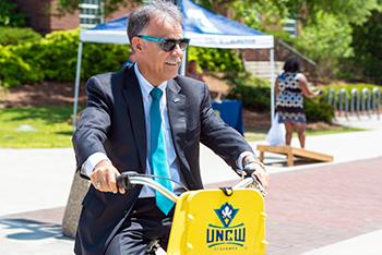 Chancellor Jose V. Sartarelli riding a UNCW bicycle
