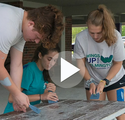UNCW students refinishing outdoor table