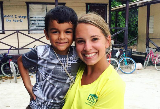 WCE student in Belize holding smiling child