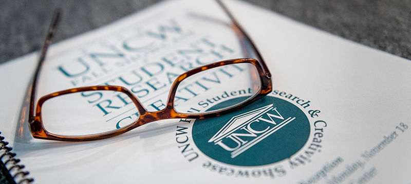 reading glasses resting on student research book