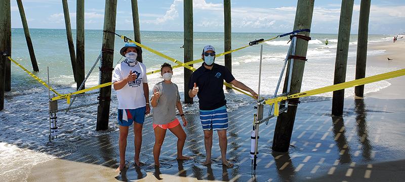 Drew Davey and students under beach pier