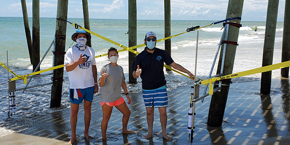 Drew Davey and students under beach pier for research